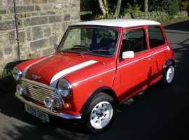 Classic 1992 Mini Cooper in red with cooper stripes.