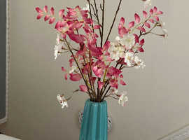Blue vase with cherry blossom flowers and leafs