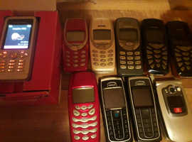 Collection of retro mobile phones and chargers.