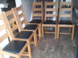 Set of 6 solid oak dining  chairs with black leather padded seats, very good condition