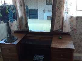 Authentic 1950s matching Retro bedroom furniture including a dressing table, a double hanging wardrobe and a 'tall boy' which has shelves and drawers.