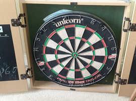Dart board in cabinet/box thingy. No darts