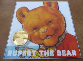 50P RUPERT THE BEAR GOLD PLATED COMMEMORATIVE COIN, SET ON RUPERT DISPLAY CARD.COMMEMORATIVE COIN