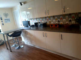 Cream gloss kitchen for sale with grey work tops, breakfast bar, and all appliances.