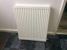 Single white radiator with thermostat valve