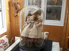 glass dome with ceramic doll.