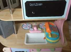 Toy kitchen unit for sale with play food and other related play items.