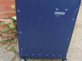 Blue American Tourister suitcase full of my son's clothes