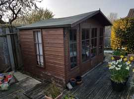Chalet style wood summer house. Double front doors with an opening window on the side