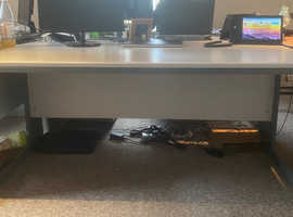 One extra large, grey, office desk, without drawers.