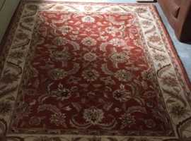 almost new tapestry rug in shades of burnt orange, cream and orange red, in perfect condition