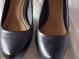 Unusual front to these black shoes, in good condition