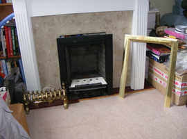 Gas fire with coals and fireplace surround in white.